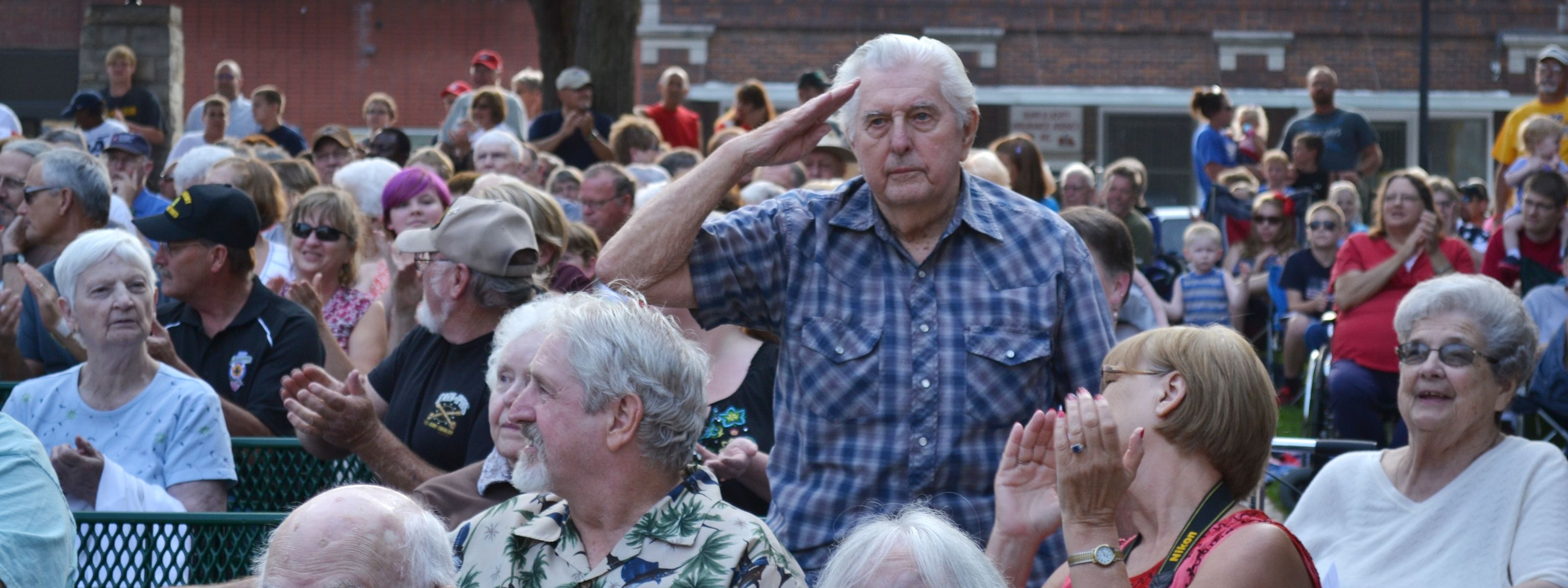 Man saluting in the crowd at the Bandshell in Seward, Nebraska on July 4th